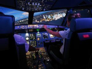 Flug im A320 Flugsimualtor über eine Stadt abends.