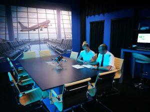 Herr Schneider am Tisch bei Taylor Air vor dem A320 Flugsimulator.